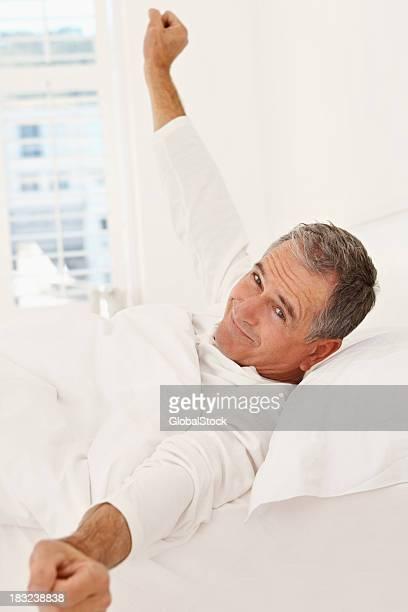 Sorridente uomo anziano appena svegliato a letto