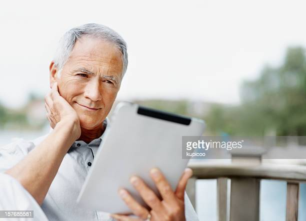 Smiling senior man looking at tablet PC screen