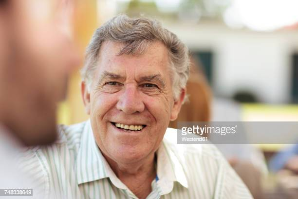 Smiling senior man socializing on a garden party