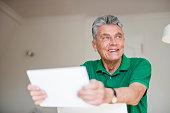 Smiling senior man using digital tablet at home