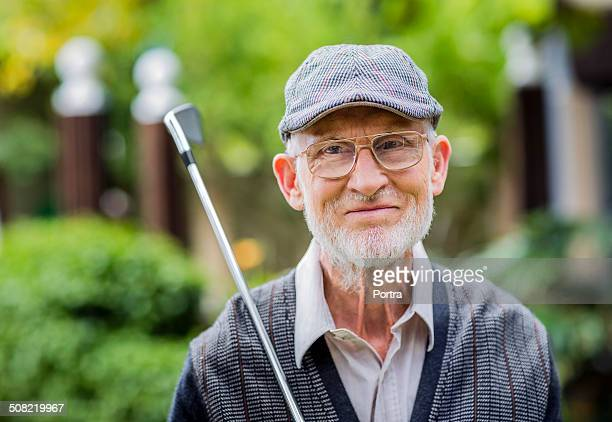 Smiling senior man with golf club