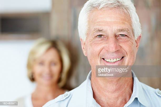 Smiling senior man with wife in the background
