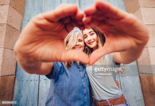 Smiling senior mother and daughter making a heart shape with their hands