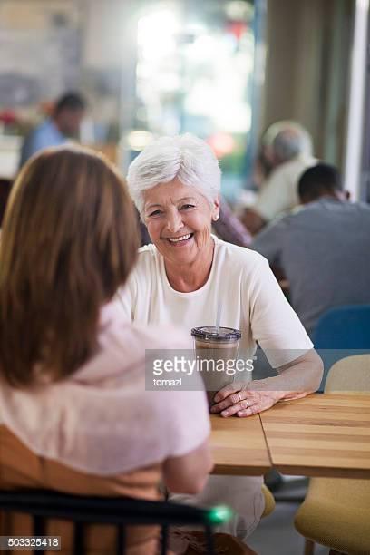 senior sorridente mãe e sua filha no caffee