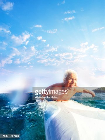 Smiling senior on a surfboard