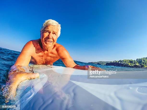 senior sorridente su una tavola da surf