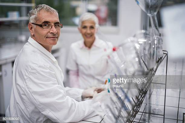 Smiling senior scientist with his colleague in laboratory.