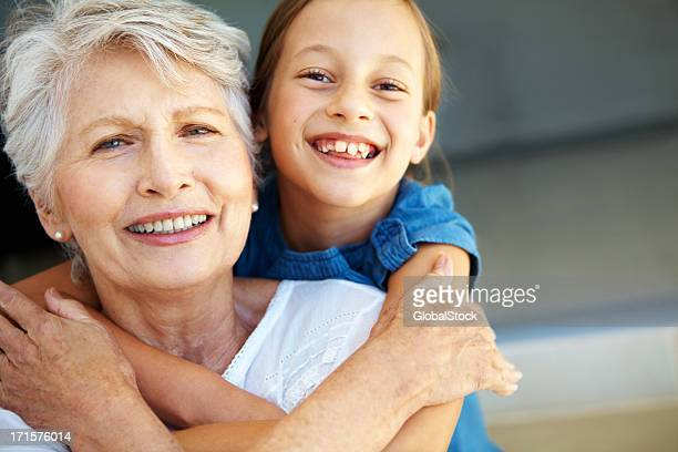 Smiling senior woman and girl embracing