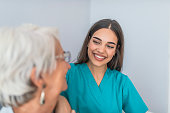 Young experienced doctor and older female patient. Image of elderly woman having professional medical care. Smiling senior woman and her young pretty caregiver