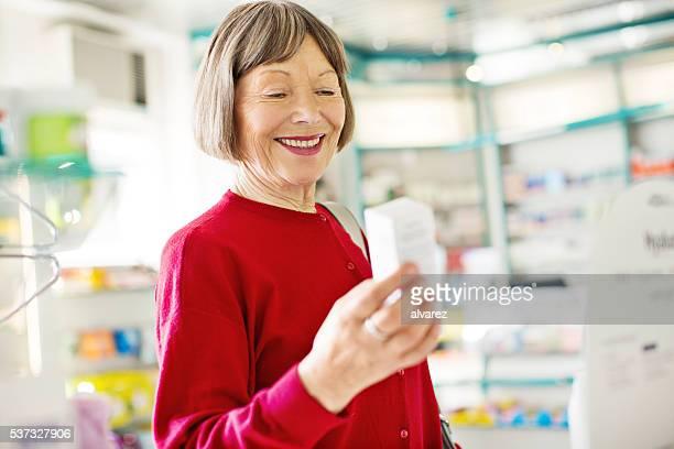 Femme âgée souriante acheter des médicaments