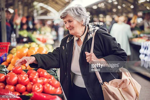 Smiling senior woman buying vegetables at farmer's market.