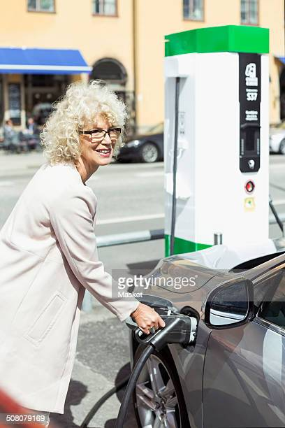 Smiling senior woman filling car with petrol at gas station