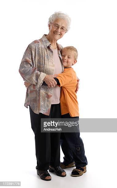 Smiling senior woman hugging smiling little boy