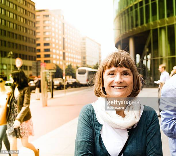 Smiling senior woman in the city (Potsdamer Platz, Berlin, Germany)