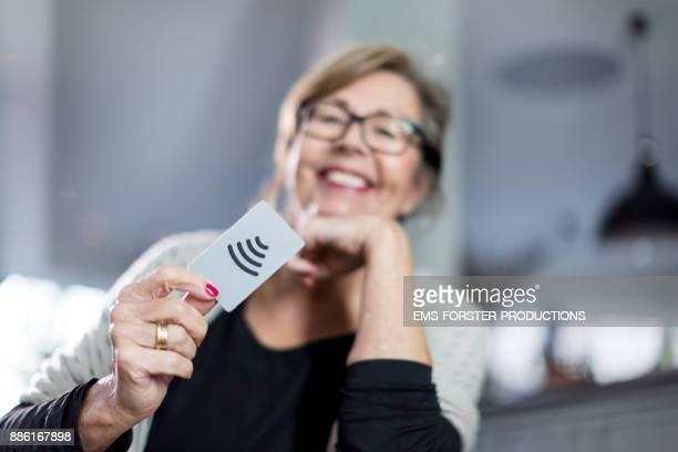 Smiling senior woman is paying cashless