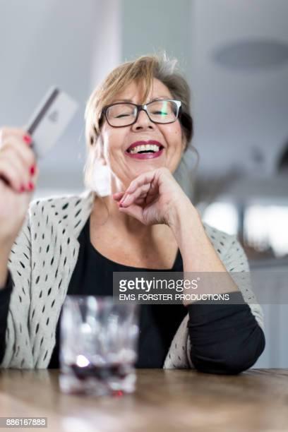Smiling senior  woman  paying cashless