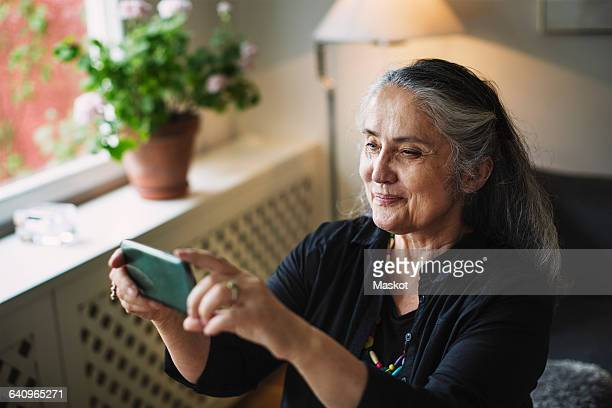 Smiling senior woman photographing through mobile phone