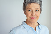 Closeup face of senior business woman standing against grey background with copy space. Portrait of successful woman in blue shirt feeling confident and looking at camera. Happy mature woman face stan