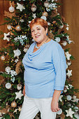 Smiling senior woman posing near christmas tree, vertical photo