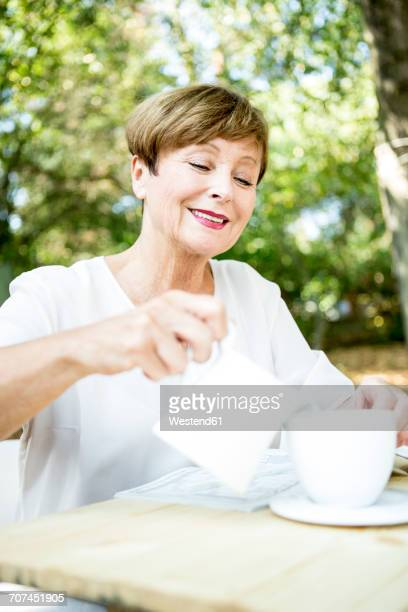 Smiling senior woman pouring milk into cup of coffee outdoors