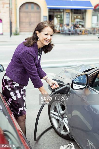 Smiling senior woman refueling car on street