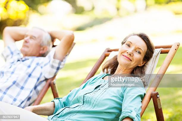 Smiling Senior Woman Relaxing On Deck Chair At Garden