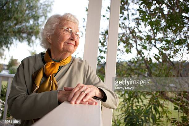 Smiling senior woman resting on a porch.