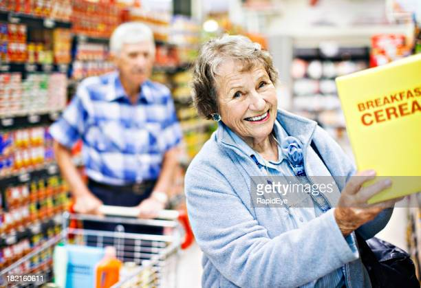 Smiling senior woman selects cereal as husband looks on