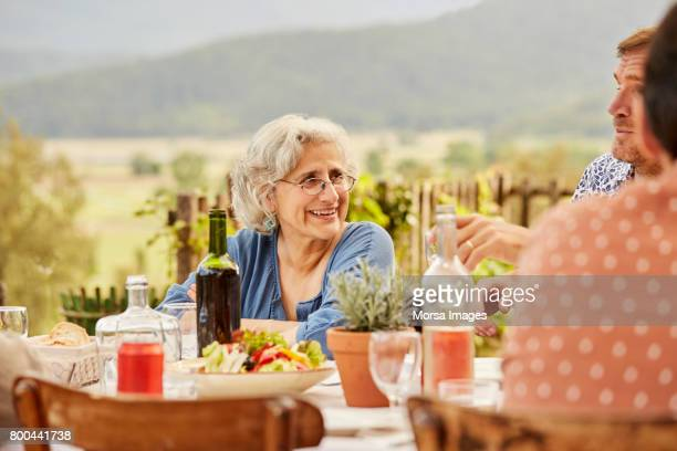 Smiling senior woman sitting with family at lunch