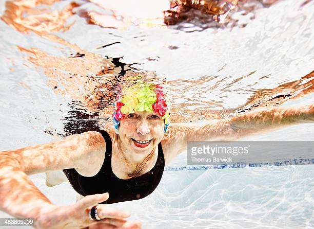 Smiling senior woman swimming in pool