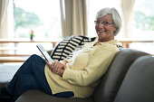 Portrait of smiling senior woman using digital tablet on sofa in living room