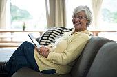 Portrait of smiling senior woman using digital tablet on sofa in living room