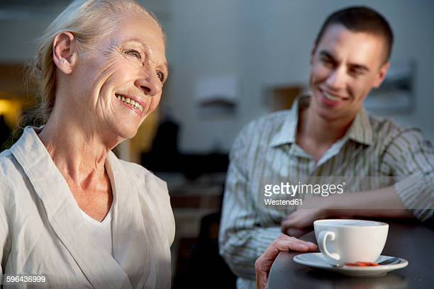 Smiling senior woman with cup of coffee and young man in background