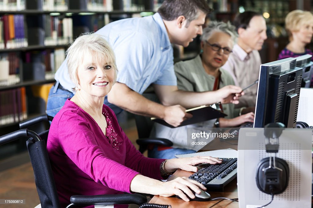 Smiling Senior Woman with Wheelchair at Computer in Library