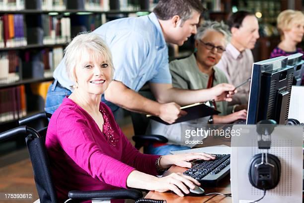 Sorridente Mulher Idosa em cadeira de rodas em um computador na biblioteca