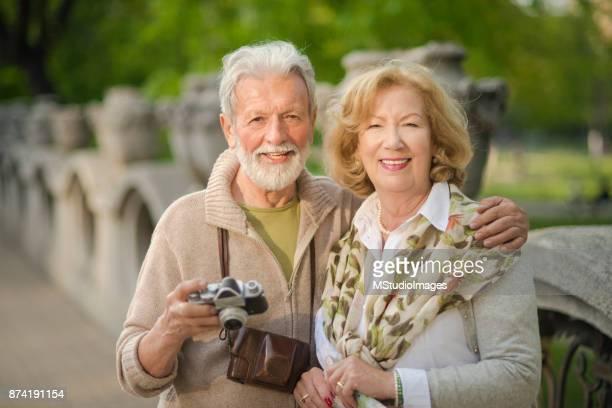 Leende seniorer tittar på kameran