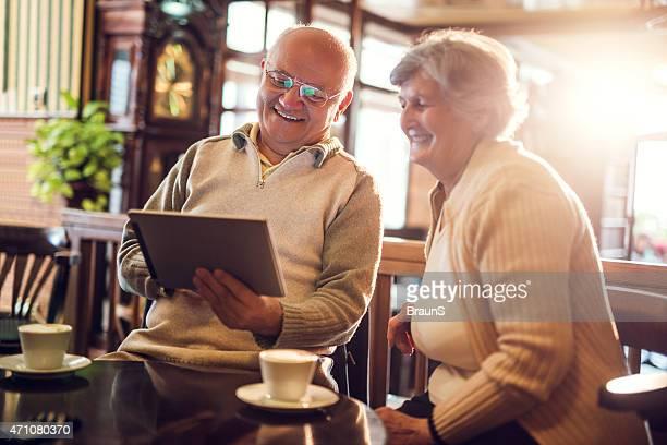 Lächelnd Senior mit tablet PC in einem Café.