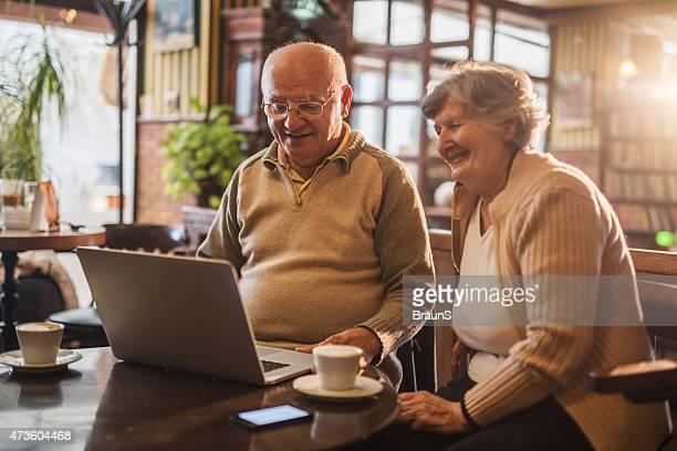 Smiling seniors using laptop while enjoying in a cafe.