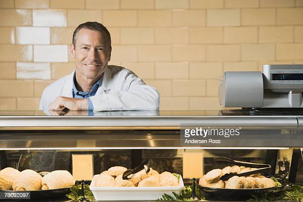 Smiling shop assistant leaning on counter top, portrait