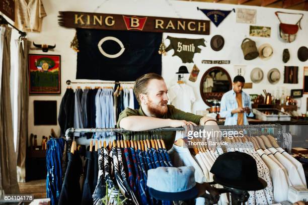 Smiling shop owner in discussion with customer in shop