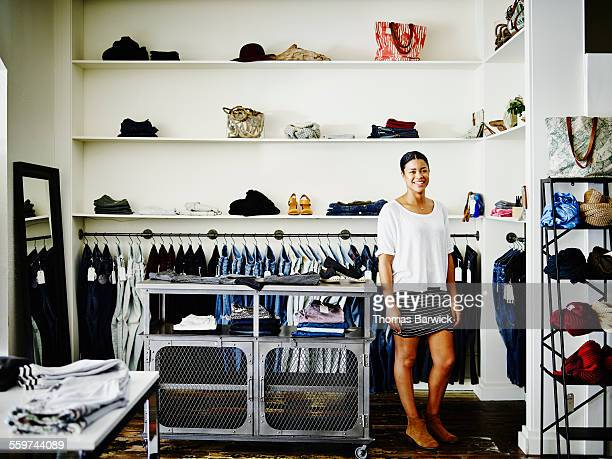 Smiling shop owner standing in boutique