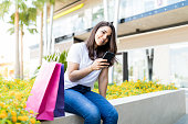 Smiling shopaholic woman social networking on mobile phone outside shopping mall