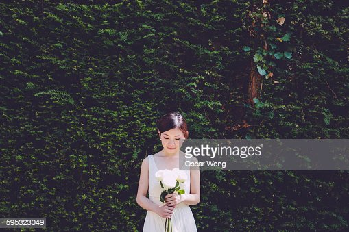 Smiling shy bride holding bouquet