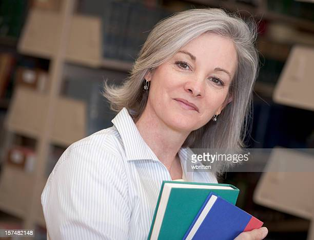 Smiling silver-haired woman holding books in a library