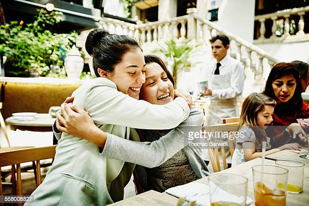 Smiling sisters embracing during family dinner