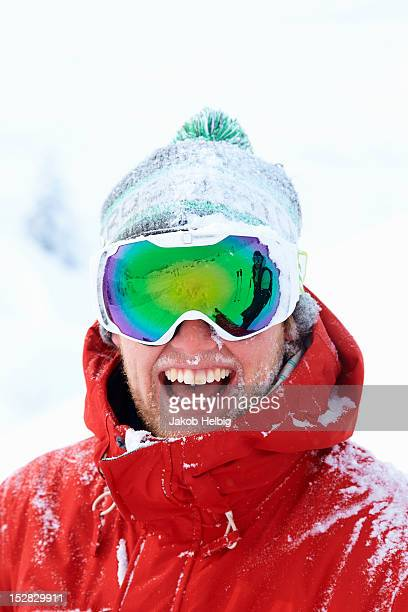 Smiling skier covered in snow