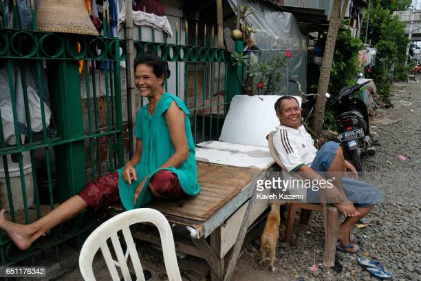A smiling slum dweller couple sit outside their shanty home by the rairoad track in Kota City on November 25 2016 in Jakarta Indonesia The slum...
