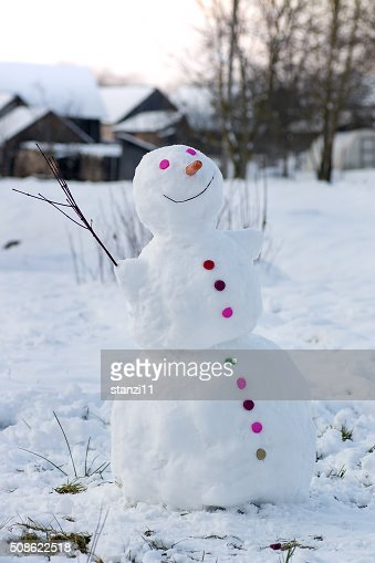 Smiling snowman in a village : Stock Photo