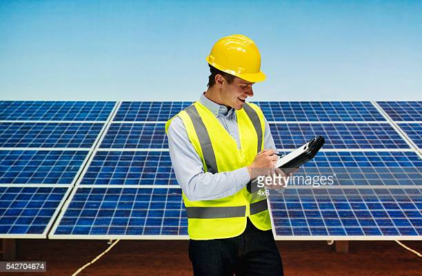 Smiling solar worker writing on clipboard