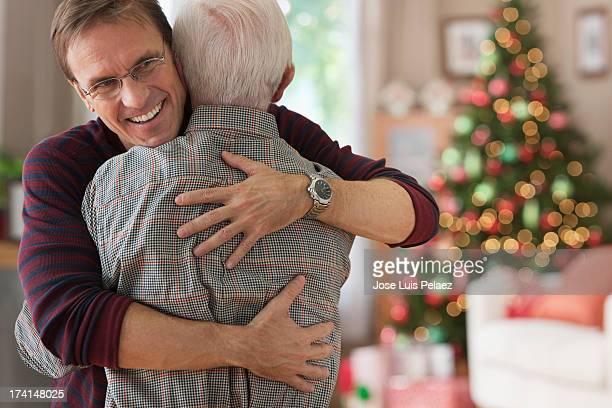 Smiling son hugging his dad at Christmas